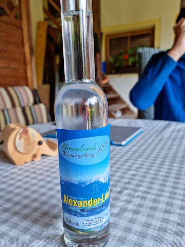"""Andreas Fischer schenkt mir zur Begrüßung einen selbstgebrannten Birnenschnaps mit dem Logo """"Almenland Mieminerberg"""" im Etikett. (Foto: Knut Kuckel)"""